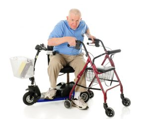A senior man transferring from his electric scooter to his wheeling walker